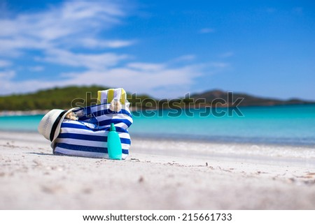 Stripe bag, straw hat, sunblock and towel on white tropical beach