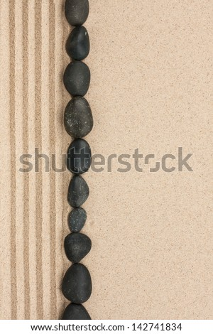 Stripe of black stones lying on the sand with space for text