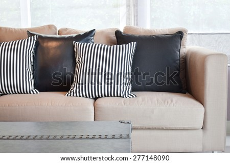 Striped and black leather pillows on velvet beige sofa in modern industrial style living room - stock photo