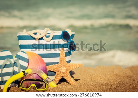 Striped bag, starfish and flip-flops on the beach. Summer vacation concept. Retro toned image