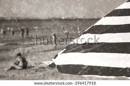 Striped beach umbrella and blurred people at background. Trouville-sur-Mer (Normandy, France). Selected focus on umbrella. Retro aged photo with scratches. Black and white. - stock photo