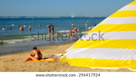 Striped beach umbrella and blurred people at background. Trouville-sur-Mer (Normandy, France). Selected focus on umbrella.  - stock photo