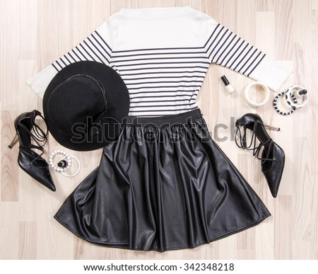 Striped blouse and leather skirt with accessories arranged on the floor. Woman black and white accessories, high heels, hat, necklace and nail polish lied down. - stock photo