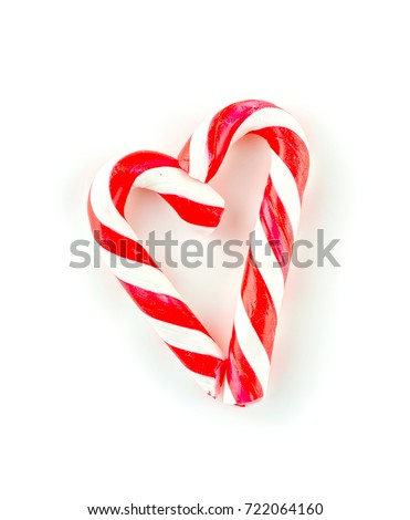Striped candy cane sticks arranged in a love heart shape on white