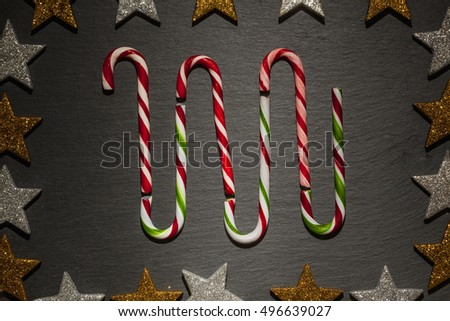 Striped candy canes on dark slate background with frame of golden and silver stars, Christmas decoration.