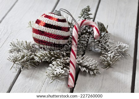 Striped christmas bauble and candy cane and fir twig on wooden background - stock photo