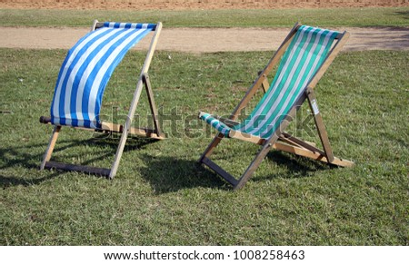 Striped Deckchairs On Grass In A Park