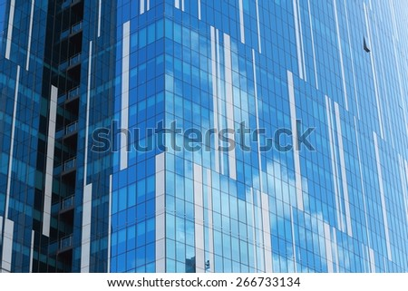 Striped glass facade of an urban office building reflecting clouds in the sky on a sunny day - stock photo