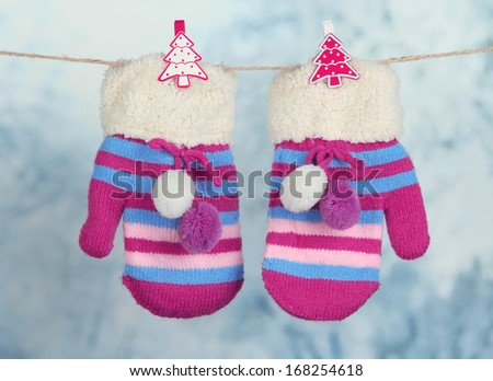Striped mittens hanging on clothesline on bright background