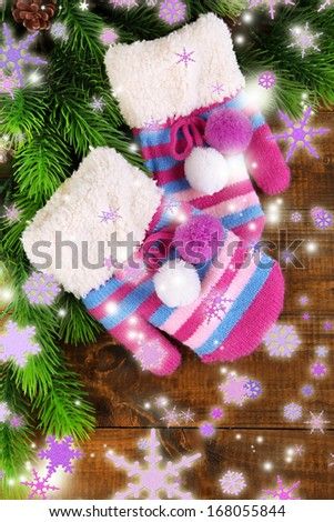 Striped mittens with fir wooden background