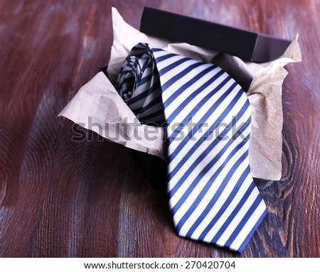 Striped necktie in box on wooden background - stock photo