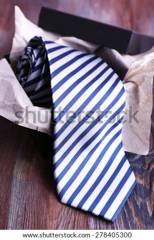 Striped necktie in box on wooden table, closeup - stock photo