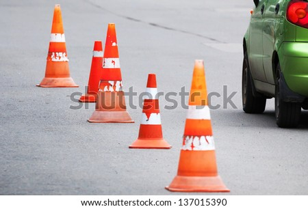Striped orange cones and car fragment on the asphalt road - stock photo
