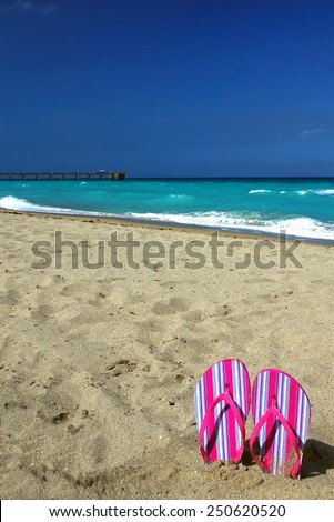 Striped Pink Sandals stuck in the Sand on Dania Beach, Florida with the Fort Lauderdale Pier in the Background. Plenty of Room for Copy in the Cloudless Blue Sky - stock photo