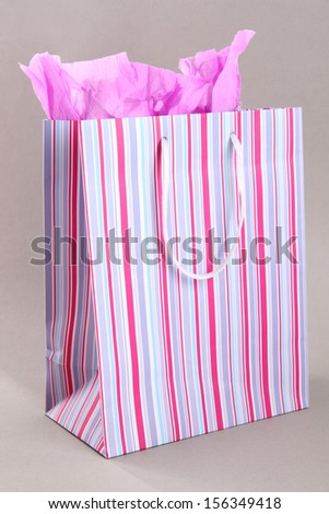 Striped shopping bag on grey background