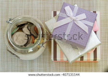 Striped, silver and purple gift boxes stacked together beside glass jar filled with coins on textured background. Selective focus to emphasize. Concept of saving for present or special occasion. - stock photo