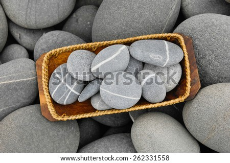 striped Stones in bowl with pebbles - stock photo