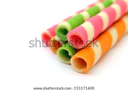 Striped wafer rolls filled with colorful isolated on white background