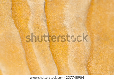 Striped wavy nature pattern and texture of close up sandy grain orange rock outdoor, backdrop, background or wallpaper with copy space. - stock photo