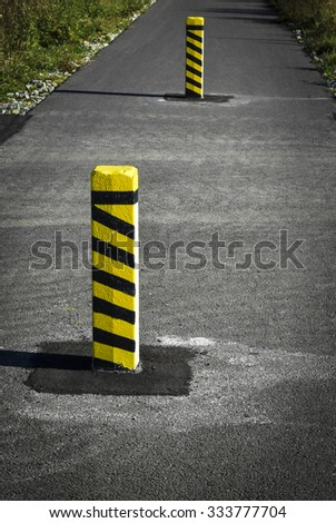 striped yellow warning concrete pillars on the road