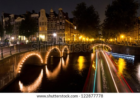 Stripes of light of a tourboat passing by on a canal in Amsterdam at night