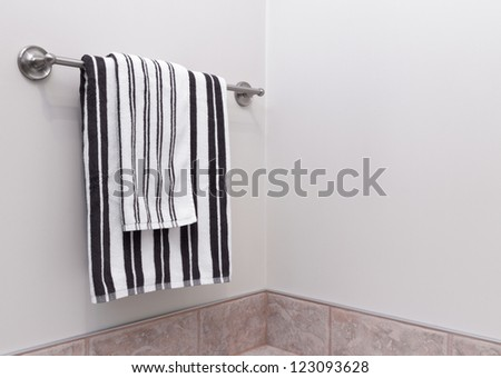 Stripped towels hanging on towel holder in the bathroom. - stock photo