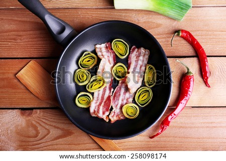 Strips of bacon in pan with shallot and chili pepper on wooden planks background - stock photo