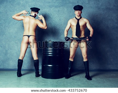 striptease dancers wearing costumes of policemen in the studio