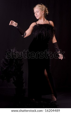 Striptease Series #2: Beautiful Blonde in Black Velvet Evening Gown Dropping her Feather Boa. - stock photo
