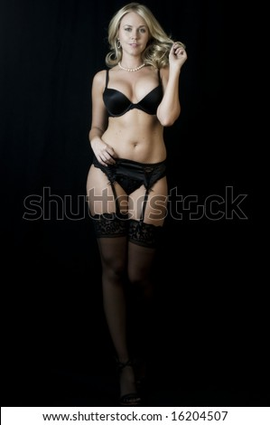 Striptease Series #8: Seductive Blonde Stripper down to her lingerie. - stock photo