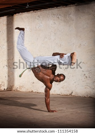 Strong African man demonstrating a Capoeria one armed kick - stock photo