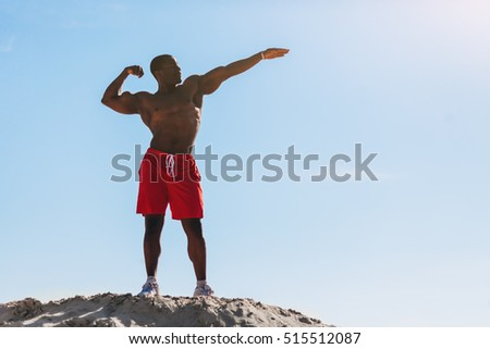 Strong Afro American man in red short shows muscles and looking upon a background blue sky