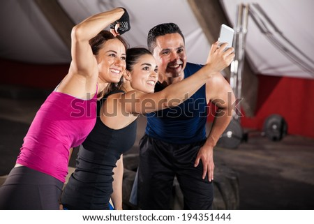 Strong and athletic Hispanic people taking a fun group selfie at a gym - stock photo