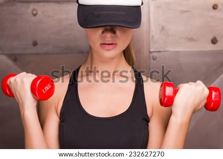 Strong and charming. Muscular woman holding dumbbells and wearing cap  while standing against metal background - stock photo