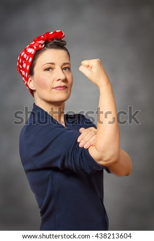 Strong and confident woman with a  red headscarf and a clenched fist, vintage or retro effect of the 50s in America, gray background, copyspace - stock photo