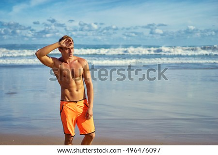 Strong and handsome. Portrait of young caucasian man on the sea beach.