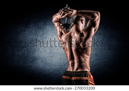 strong and handsome young man doing exercise with dumbbells - stock photo