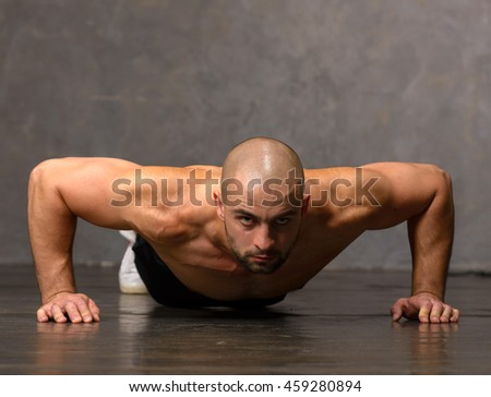 Strong and handsome young man is making push ups. Bodybuilder at work in the gym on dark background.