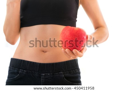 Strong and healthy woman holding fresh red apple in her left hand, wearing black sport bra and dark blue jeans and showing her small waist line facing towards camera - isolated with white background - stock photo