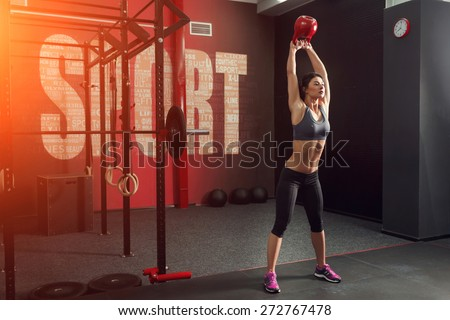 Strong and muscular young woman, brunette, holds up a red kettlebell in the gym - stock photo