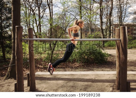 Strong and physically fit young woman doing triceps dips on parallel bars at park. Caucasian fitness female exercising outdoors. - stock photo