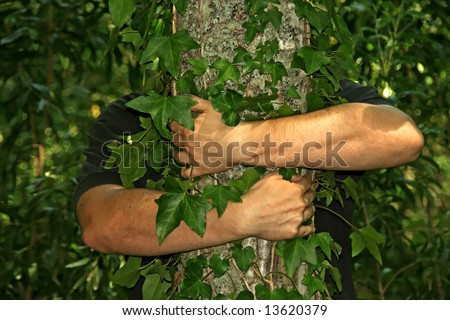 strong arms of a man, hugging a tree, with green vegetation as background