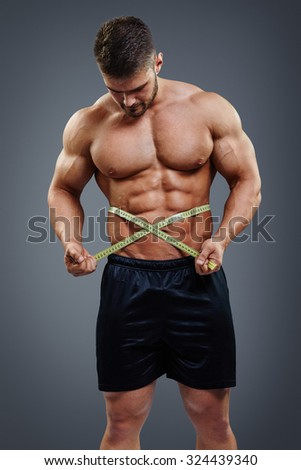 Strong athlete measuring his waist with tape measure isolated over gray background. Six pack abs result concept. - stock photo