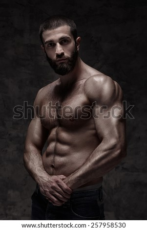 strong athletic beardy man on dark grey background - stock photo