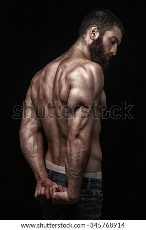 strong athletic beardy mans back isolated over black background - stock photo