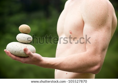 Strong athletic hand holding a pile of stones in balance. Get the balance concept. - stock photo