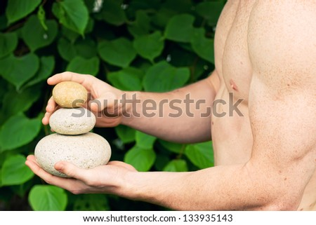 Strong athletic hand holding a pile of stones in balance. Get the balance concept.