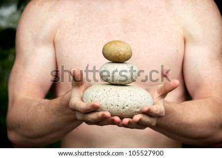 Strong athletic hands holding a pile of stones in balance. Get the balance concept. - stock photo