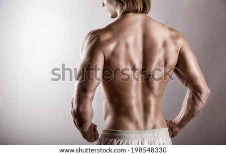 Strong athletic man back on a gray background - stock photo