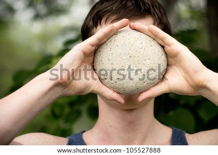 Strong athletic man covering his face with a stone. - stock photo